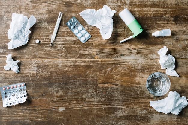Visão elevada de medicamentos; papel de seda amassado; termômetro; spray de garganta e copo de água no pano de fundo de madeira Foto gratuita