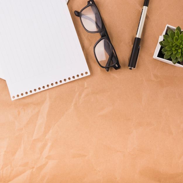Visão geral da página única; óculos; caneta e vaso de plantas em papel pardo Foto gratuita