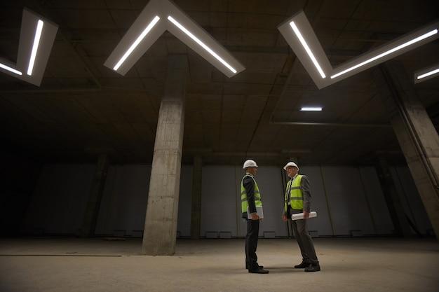 Visão grande angular de dois empresários vestindo capacetes discutindo um acordo de investimento enquanto estavam em um local de construção Foto Premium