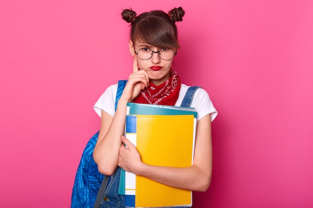 Visão horizontal da estudante pensativa bolsas lábios, mantém o dedo indicador no queixo, usa óculos redondos, bandanas no pescoço, camiseta branca, macacão jeans, pensa em lição de casa, fica por cima da parede rosa. Foto Premium