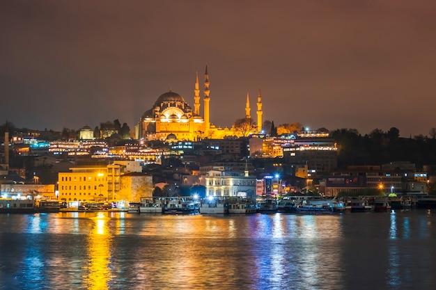 Visão noturna da paisagem urbana de istambul mesquita suleymaniye com barcos turísticos flutuantes no bósforo Foto Premium