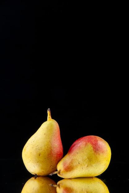 Visão vertical de amarelo maduro inteiro com peras vermelhas sobre fundo preto Foto gratuita