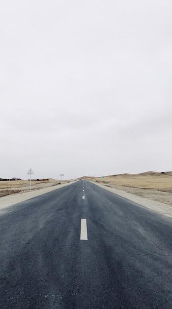 Visão vertical de uma estrada estreita no meio do campo sob um céu claro Foto gratuita