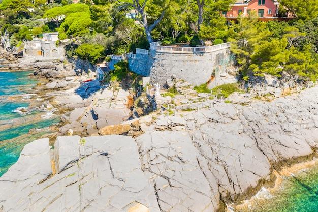 Vista aérea da cidade com as casas coloridas localizadas na costa rochosa do mar da ligúria, camogli perto de gênova, itália. rocky coastline é lavado com água azul turquesa. Foto Premium