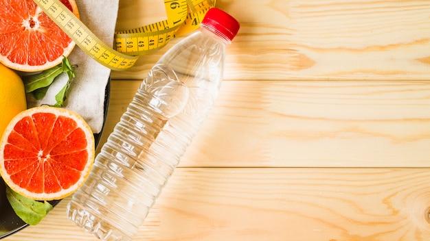 Vista aérea da garrafa; fita métrica e frutas cítricas em fundo de madeira Foto gratuita