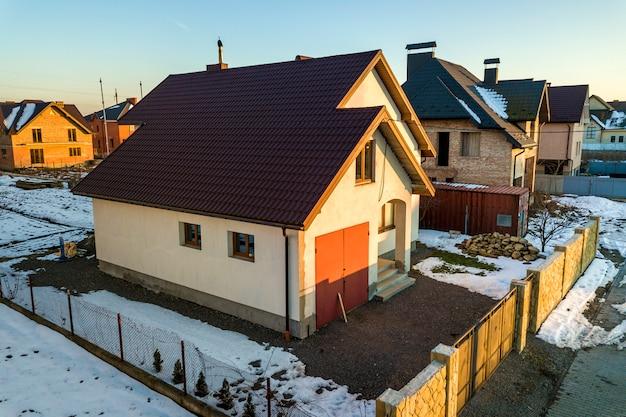 Vista aérea da nova casa residencial casa e garagem anexa com telhado de telha no quintal cercado num dia ensolarado de inverno na moderna área suburbana. investimento perfeito na casa dos sonhos. Foto Premium