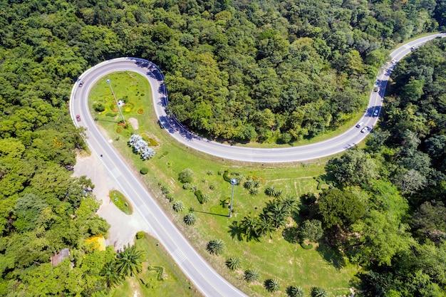 Vista aérea de carros estão passando por uma estrada curva na montanha Foto Premium