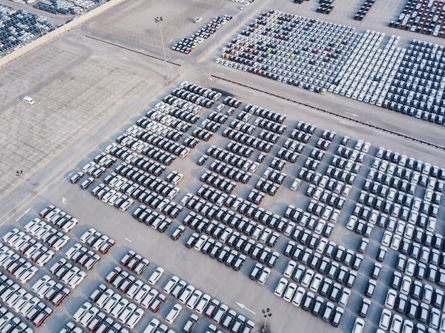 Vista aérea de carros novos estacionados na área de estacionamento da fábrica de automóveis. Foto Premium