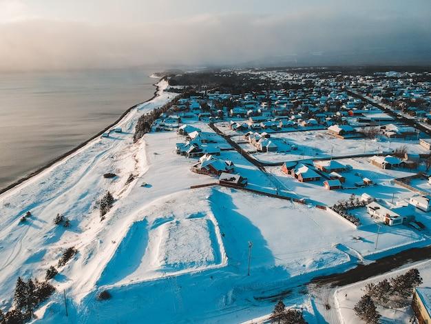 Vista aérea de casas e campo coberto de neve, vendo o corpo de água sob o céu branco Foto gratuita