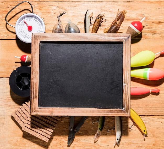 Vista aérea, de, em branco, madeira, ardósia, sobre, a, equipamento pesca, ligado, escrivaninha madeira Foto gratuita