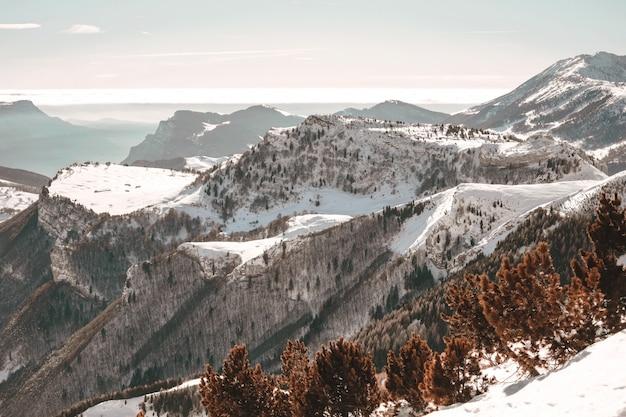 Vista aérea de montanhas cobertas de neve sob o céu azul claro Foto gratuita