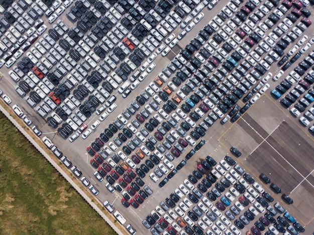Vista aérea de novos carros estacionados na área de estacionamento da fábrica de automóveis Foto Premium