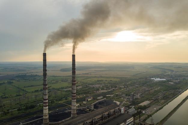 Vista aérea de tubos de chaminé alta com fumaça cinza da usina de carvão. produção de eletricidade com combustível fóssil. Foto Premium