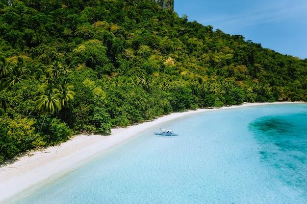 Vista aérea de um barco atracado em uma praia isolada de areia branca com águas azul-turquesa e coqueiros Foto Premium