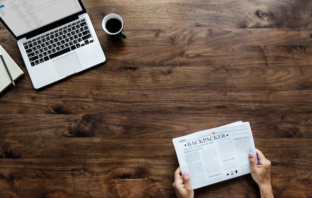 Vista aérea, de, um, leitura mulher, um, jornal, e, computador, laptop, ligado, tabela madeira Foto gratuita
