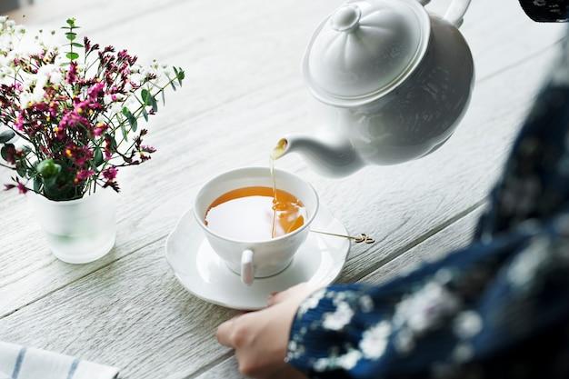 Vista aérea, de, um, mulher, despejar, um, chá quente, bebida Foto gratuita