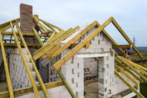 Vista aérea de uma casa particular com paredes de tijolos de concreto aerado e estrutura de madeira para telhado futuro. Foto Premium