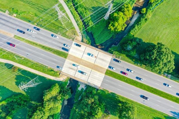 Vista aérea de uma ponte sobre o riacho e linhas de alta tensão com carros na estrada Foto gratuita
