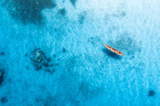 Vista aérea do barco de pesca na água azul transparente Foto Premium