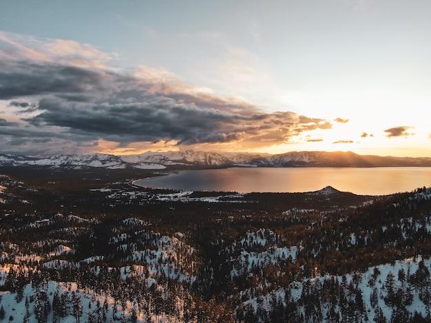 Vista aérea do belo lago tahoe capturada em um pôr do sol nevado na califórnia, eua Foto gratuita