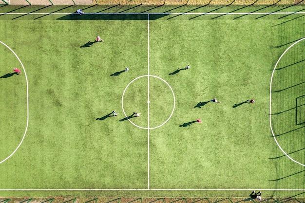 Vista aérea do campo de esportes de futebol verde e jogadores jogando futebol Foto Premium