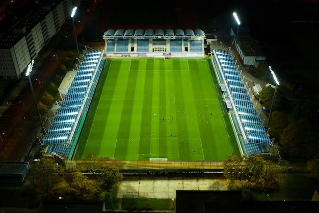 Vista aérea do campo de futebol ou futebol enquanto atletas ou jogadores estão treinando à noite sob luzes brilhantes do estádio, praga 15.11.2019 Foto Premium