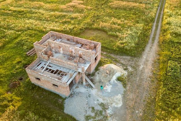Vista aérea do canteiro de obras da futura casa, piso do porão de tijolos e pilhas de tijolos para construção. Foto Premium