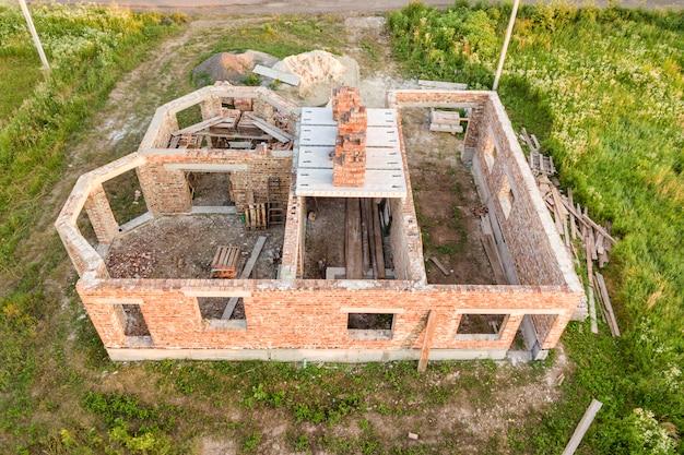 Vista aérea do canteiro de obras para a futura casa, piso do porão de tijolos e pilhas de tijolos para construção. Foto Premium