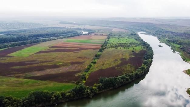 Vista aérea do drone da natureza na moldávia, rio flutuante com o céu refletido, campos verdes com árvores, névoa no ar Foto gratuita