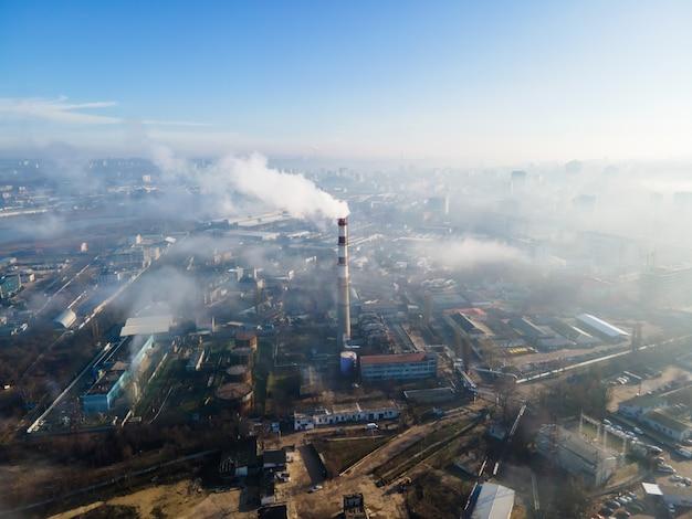 Vista aérea do drone de chisinau. estação térmica com fumaça saindo do tubo. edifícios e estradas. nevoeiro no ar. moldova Foto gratuita