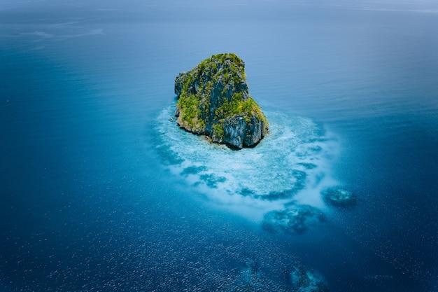 Vista aérea do drone de uma ilha isolada do penhasco, rodeada por um oceano azul turquesa. el nido, palawan. Foto Premium