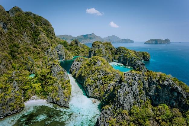 Vista aérea do drone turquesa de grandes e pequenas lagoas cercadas por rochas íngremes, reserva nacional marinha em el nido, palawan. Foto Premium