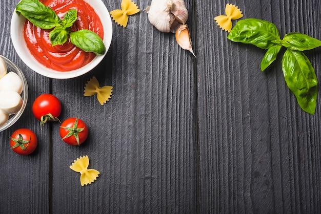 Vista aérea do molho de tomate com mussarela; massa; alho um manjericão na prancha de madeira Foto gratuita