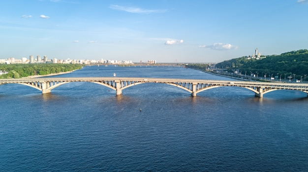 Vista aérea do zangão da ponte ferroviária metro com trem e dnieper. skyline da cidade de kiev, ucrânia Foto Premium