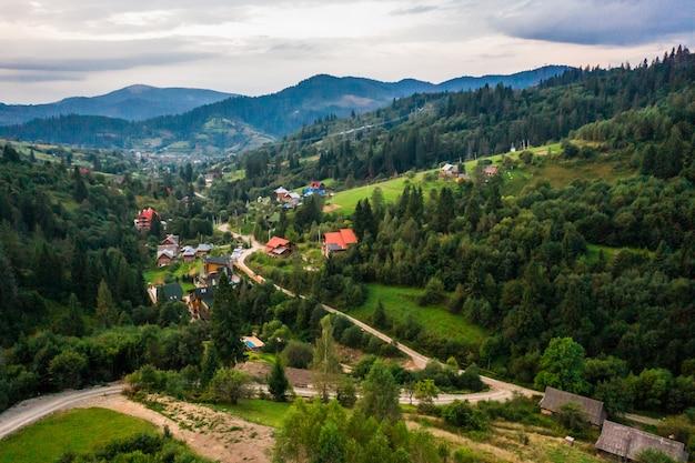 Vista aérea, filmado por drone village pequeno entre montanhas, florestas, campos de arroz Foto gratuita