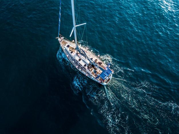 Vista aérea superior aérea de barco à vela de luxo na lagoa de água do mar azul cristalino Foto Premium