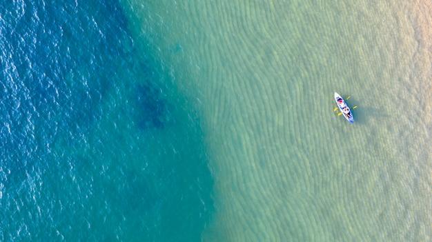 Vista aérea superior de caiaque em torno do mar com sombra água azul esmeralda e espuma de onda Foto Premium