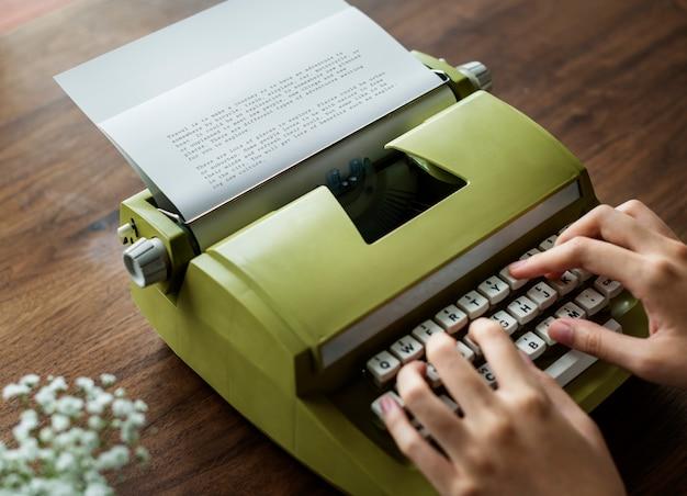 Vista aérea, um, mulher, usando, um, retro, typewriter Foto gratuita