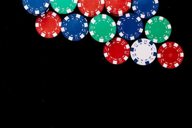 Vista alta ângulo, de, coloridos, lascas poker, ligado, experiência preta Foto gratuita
