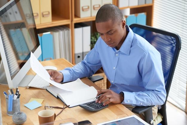 Vista alta ângulo, de, contador masculino, verificar documento financeiro Foto gratuita