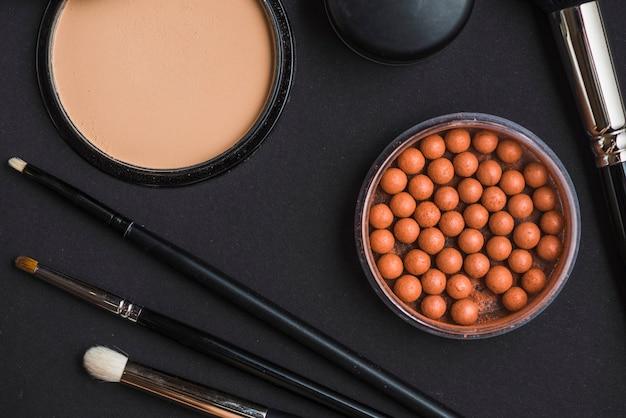 Vista alta ângulo, de, cosmético, produtos, com, escova maquiagem, ligado, pretas, fundo Foto gratuita