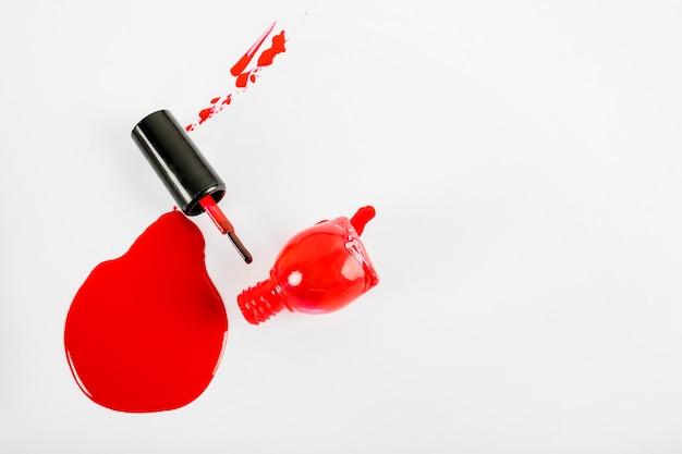 Vista alta ângulo, de, derramado, vermelho, esmalte vermelho, branco, fundo Foto gratuita