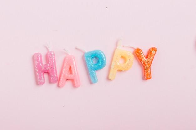 Vista alta ângulo, de, feliz, palavra, velas, ligado, fundo cor-de-rosa Foto gratuita
