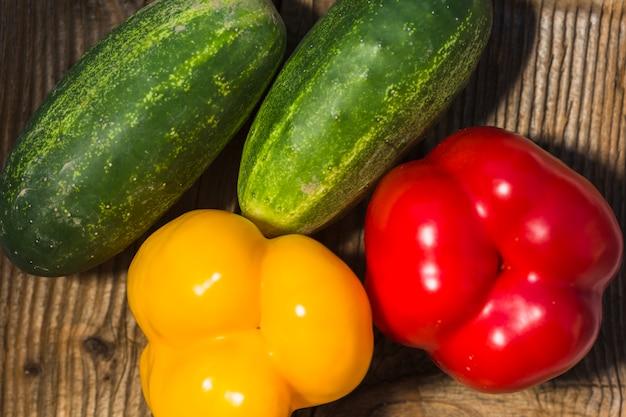 Vista alta ângulo, de, fresco, pepinos, e, coloridos, pimentas Foto gratuita