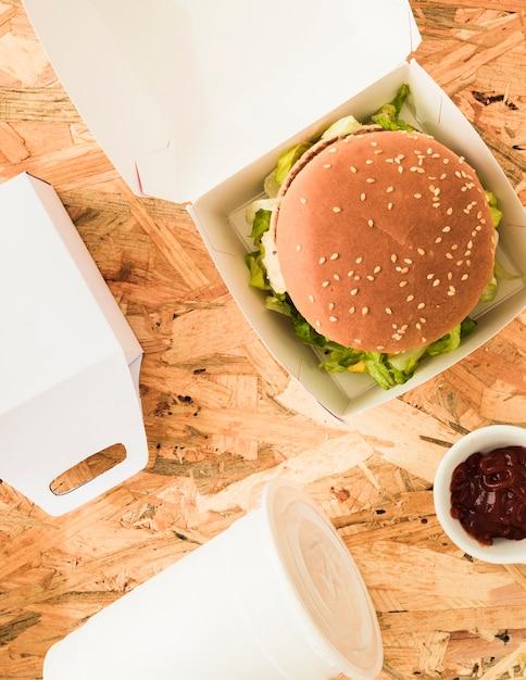 Vista alta ângulo, de, gostosa, hambúrguer, com, copo disposição, e, alimento, pacote Foto gratuita