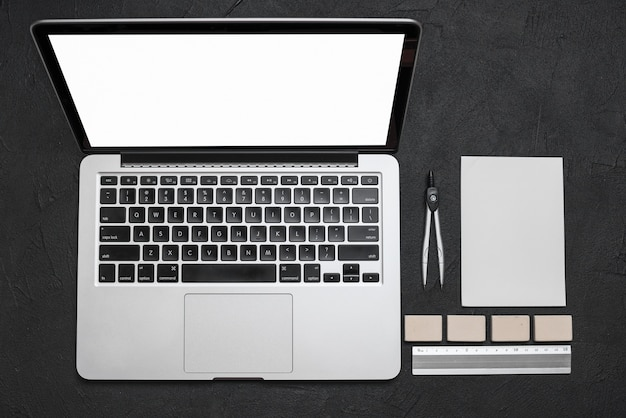 Vista alta ângulo, de, laptop, e, stationeries, ligado, experiência preta Foto gratuita