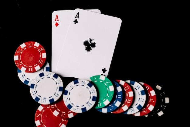 Vista alta ângulo, de, lascas pôquer, e, dois, ases, cartas de jogar, ligado, pretas, fundo Foto gratuita