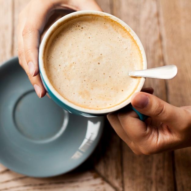 Vista alta ângulo, de, mão mulher, segurando, copo café, com, espumoso, espuma Foto gratuita