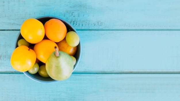 Vista alta ângulo, de, vário, suculento, frutas, em, tigela, ligado, azul, tampo madeira Foto gratuita
