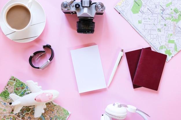 Vista alta ângulo, de, vários, viajante, acessórios, com, xícara chá, ligado, fundo cor-de-rosa Foto gratuita